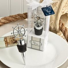 Ship's Wheel Wine Bottle Stopper Wedding Favor features a long conical base wrapped with a black rubber gasket for a tight seal. The top of the wine bottle stopper features a metal charm in the shape of a ship's wheel. It comes packaged in a clear box with a nautical themed bottom and backing. It is wrapped in a whit organza ribbon tied into a bow on top with an attached favor tag.
