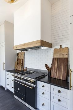 A White Kitchen Hood Accented With Rustic Wood Trim Is Mounted On An Exposed Love The Aga Stove Black S And Painted Brick