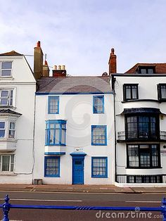 The exterior of a residential building with blue door and window frames in Eastbourne, Sussex, England.