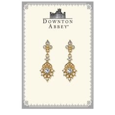 Dropping down from a trifecta of white diamond glass crystals at the post, a unique charm pendant is covered with faux pearls that jut out from an embellished gold tone base with a dazzling glass crystal at the center. Presented in a Downton-Abbey themed gift box.