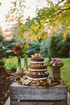 "Bohemian-style cake table with ""naked"" fruit cake, berries, and flowers"