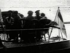 The Imperial family sitting on a boat with officers. On the left it is Anastasia; Olga is on her right; Tatiana is seen on the other side of the boat in between them; Nicholas is sitting next to Olga; Maria is looking at the camera on the far right; Alexandra is between Maria and Tatiana.
