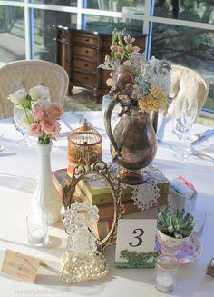 Vintage table scape one of a kind decor from Rent My Dust vintage rentals Romantic Secret Garden Wedding, Silver teapot, pearls perfume bottles, lace, teacups tea party wedding, rentmydust.com succulent, birdcage
