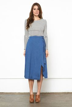 The Infinity Skirt is a midi wrap skirt that ties up at the waist with an open front split in a classic blue denim fabric. Made by Aussie brand The Fifth Label, this is a unique and season-less staple