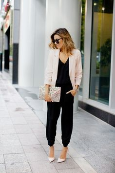 Christine Andrew is wearing a black jumpsuit from Revolve Clothing, pink blazer from Forever 21, clutch from Nila Anthony and pink shoes.