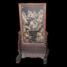 "Lot #203: Chinese Jade Screen DESCRIPTION: A wooden decorative wall panel inlaid with jade carvings of a horse, an ox, and flowers. A floral motif is carved around the frame and base. On the back is a painting of a mountainous, watery landscape outlined in gold paint. Displayed on the front is a message that bestows good luck onto the viewer. CIRCA: Late 19th Early 20th ct. ORIGIN: China DIMENSIONS: 32 1/2"" L x 23 3/4"" W x 59 1/4"" H"