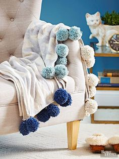 Make a stylish addition to a purchased throw by adding jumbo pom-poms to the edges. Use an extra-large pom-pom maker to make 4½-inch balls, leaving long tails when tying each one off. Pin the yarn tails along the edge of the throw, roll the hemmed edge to enclose the tails, and topstitch.