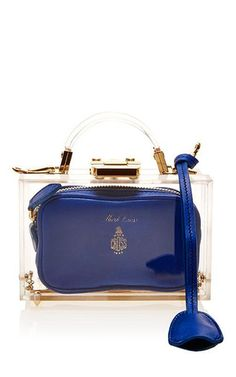 America's first luxury leather goods brand traces its heritage back to 1845, and draws from its vintage archives for its distinctly glamorous designs. This handbag by **Mark Cross** features a new take on the trunk style that first gained fame and exposure as Grace Kelly's namesake accessory of choice, and features a plexiglass outer and a soft smooth sapphire leather pouch on the inside.