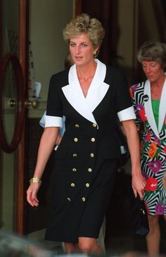 Princess Diana attends the 1994 Wimbledon ladies' singles tennis final with Prince William in June 1994. She wears a black double-breasted dress with white collar and short sleeves. The dress is fastened with two rows of golden buttons.