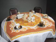 he 1970s table featured a tablecloth and tableware in earthy tones of orange and brown.