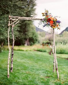 A natural Aspen wood structure accented with a cluster of various eucalyptus, dahlias, ferns, curly willow branches, clematis, and roses served as Whitney and Matt's arch.