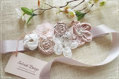 This beautiful,natural looking sash is made of satin and chiffon rosettes with pearls, crystals and rhinestones. Each flower is carefully handmade