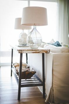 Loving the bubble glass lamp bases, the basic couch cover with pillow color pops, the rustic table top, and the use of shells.  {via: House of Turquoise: Ashley Gilbreath Interior Design}