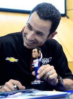 Helio Castroneves poses with a bobble-head doll in Birmingham Alabama, April, 2013.