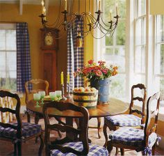 French country dining room with mustard / gold / yellow walls and blue checked curtains & chair cushions
