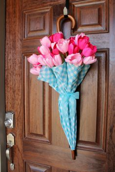 This simple spring wreath took 10 minutes to assemble.  All you need is an umbrella with a curved handle (check out Hobby Lobby's Spring section for a wide array of colors and styles on the cheap),  2 bunches of mixed silk tulips (Michael's), and coordinating ribbon (I used sheer wired ribbon I had in my gift wrapping bag).  I hope this wreath convinces mother nature to allow Spring to finally arrive in North Texas #spring #wreath #diy #tulips #umbrella