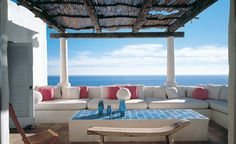 White, coral and blue outdoor space overlooking the ocean