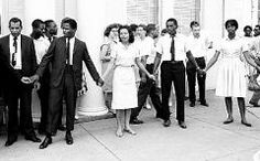 Diane Nash, Leads a group of students in song during a protest in front of the Nashville, TN police station in 1961. The student was protesting alleged police brutality during the sit-in protest of the city's segregated lunch counters.
