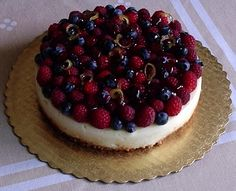 Mascarpone Cheesecake topped with fresh blueberries, raspberries and candied lemon zest