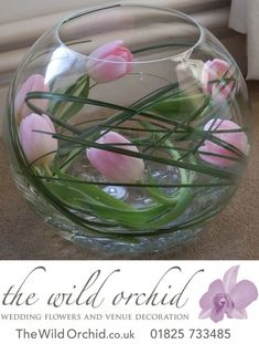 So simple and yet so effective! A fishbowl vase with bear grass and pink tulips wrapped around the inside of … Fish Bowl Centerpiece Wedding, Fishbowl Centerpiece, Simple Wedding Centerpieces, Flower Centerpieces, Flower Decorations, Centrepieces, Decor Wedding, Tulip Wedding, Wedding Flowers