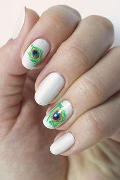 Nail art designs of a feather flock together! This peacock feather nail art design re-creates the look of the world's most exotic plumage with layers of swirling circles. Here's how to get the look.