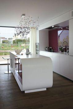 Un îlot design avec des rangements intégrés pour cette cuisine tout en longueur