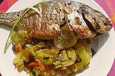 Ganzer Fisch auf Kartoffeln und Gemüse