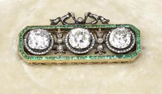 A gold, emerald and diamond brooch Fabergé, Moscow 1899-1908, scratch inventory number 29835 the openwork emerald frame shaped rectangular with canted corners, set with three diamonds divided by diamond set sprays, surmounted by diamond-set bow