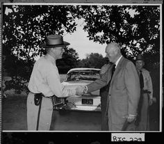 President Dwight D. Eisenhower shaking hands with Georgia State Patrol Trooper C. W. Herndon at the Augusta National Golf Course.