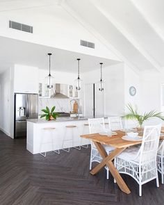 A white tropical kitchen with a marble backsplash, glass pendant lamps, wood and metal stools and a dining space with a wooden table and white rattan chairs.