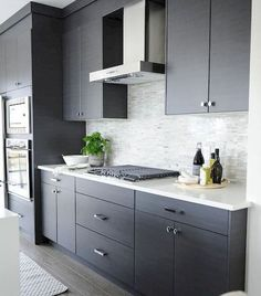 Modern Kitchen Interior Remodeling Modern gray kitchen features dark gray flat front cabinets paired with white quartz countertops and a gray mosaic tiled backsplash. Modern Grey Kitchen, Grey Kitchen Designs, Classic Kitchen, Grey Kitchens, Modern Kitchen Design, Kitchen White, Gold Kitchen, Modern Kitchens, Modern Farmhouse