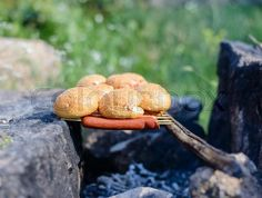 Cooking over a makeshift campfire with sausages on skewers and fresh bread rolls balanced on a stick over the coals