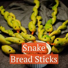 These Spooky Snake Breadsticks make a perfect addition to your Halloween Party Food table. A great healthy appetiser idea to surprise the kids and grown-ups alike. Step by step recipe to make your own breadsticks, how to shape and decorate them into snakes. Serve with your choice of sauce to dip your serpent into. Also great for Harry Potter or reptile / zoo themed party food.