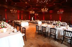 Long tables with white linens and mahogany chairs   villasiena.cc