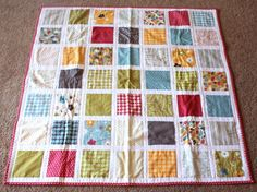 This free baby quilt pattern is easy and inexpensive to make with a charm pack and some simple white fabric for sashing. To piece the top of the Make Life Square Baby Quilt, sew charm squares to sashing for a clean, blocky design.