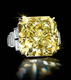 YELLOW DIAMOND:  Set with a cut-cornered modified square-cut fancy yellow diamond, weighing approximately 26.18 carats, flanked on either side by four baguette-cut diamonds, mounted in gold and platinum.  Auctioned by Christie's for $602,500
