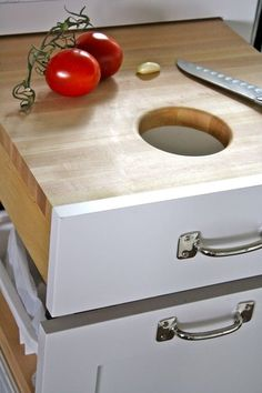 Cutting board drawer with a hole over garbage drawer.  Very smart! katielpowers