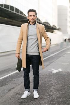 Want to become a Lookastic contributor and get paid? Contact us at team@lookastic.com. Shop this look for $294:  http://lookastic.com/men/looks/dress-shirt-and-crew-neck-sweater-and-overcoat-and-zip-pouch-and-jeans-and-low-top-sneakers/2778  — Black Dress Shirt  — Grey Crew-neck Sweater  — Camel Overcoat  — Dark Brown Leather Zip Pouch  — Black Jeans  — White Low Top Sneakers