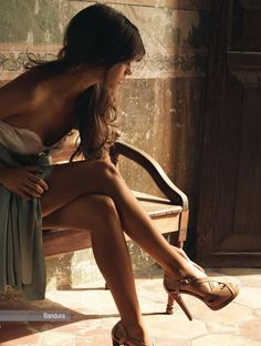 Leggy model in a strapless dress takes a moment to rearrange the straps on her fine looking ankle snappers