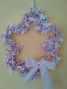 A 35cm flower shaped rag wreath, decorated with a bow, created using Cath Kidston style materials in a shabby chic style