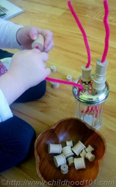 Easy sewing for tiny figures, parmesean cheese jar for storage and to hold the pipe cleaners upright as the child threads them with spools.