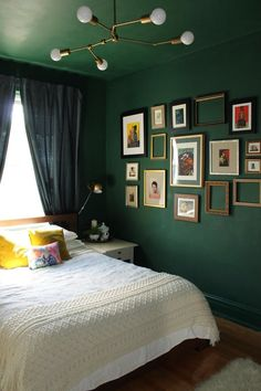 Nice bedroom design with green walls, modern chandelier, framed wall art.