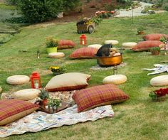 Blankets and throw pillows are scattered around a firepit, creating a cozy outdoor lounge area.