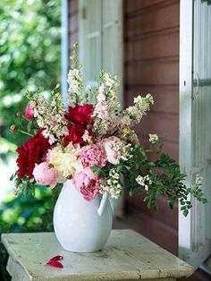 A tall white ceramic pitcher looks country-garden fresh with a loose arrangement of pretty garden peonies paired with pink larkspur and a few wild roses.