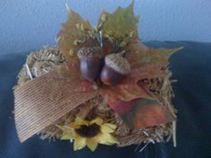 As I was cleaning up from some crafting I threw this little diddy together.  I used a small bale of straw, a decoupaged leaf from one of my trees, two of billions of acorns in my yard, scrap autumn ribbon, sprig of dried wildflower and hot glue gun. I used a straight pin to attach ribbon and leaf then hot glued acorns, sprig and sunflower to the straw bale.  That's it!!!