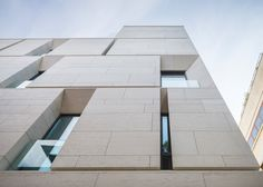 Angled openings create balconies across the facade of MORA apartments