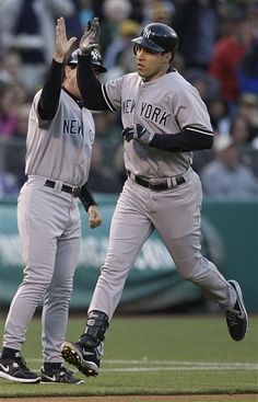 GAME 45: Friday, May 25, 2012 - New York Yankees' Mark Teixeira, right, celebrates as he passes third base coach Rob Thomson after Teixeira hit a two run home run off Oakland Athletics' Tyson Ross during the third inning of a baseball game in Oakland, Calif. (AP Photo/Ben Margot)
