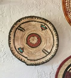 This posting is for a single hand woven African basket, made in Nigeria. Use solo or looks great paired with others! See pics for styled basket wall. This is a vintage, round African hand woven basket in black, teal, maroon/rust and natural colors. This basket is made with tightly woven straw into with some beautiful geometric detail. Made in Nigeria, Africa.  Add this lovely piece to your southwestern basket wall or use to hold fruit, bread, earrings, bracelets, or other small items. Di...
