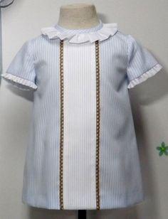 Vestido para bebe niña en pique de rayas celeste con centro de jaretas blanco y punta de bolillos camel, adornado con volante blanco en manga y cuello.