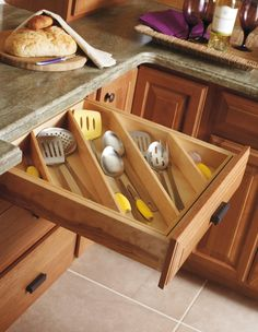 When it comes to kitchen utensil storage, you really only have two options: standing up in containers on the counter or laid flat in drawers